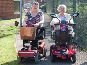 two ladies going to the shops on their scooters